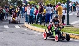 As crianças competem em torno do canto em carros de corridas de madeira caseiros Foto de Stock