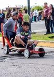 As crianças competem em torno do canto em carros de corridas de madeira caseiros Fotos de Stock Royalty Free