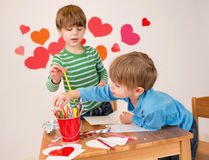 As crianças contrataram em artes do dia de Valentim com corações Fotografia de Stock Royalty Free