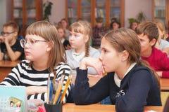 As crianças da escola na sala de aula escutam o professor fotos de stock