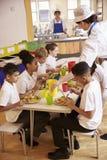 As crianças da escola primária comem o almoço no bar de escola, vertical Imagens de Stock