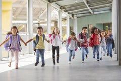 As crianças da escola primária correm manter as mãos no corredor, fim imagens de stock