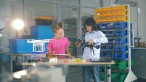 As crianças da escola trabalham junto fixando um zangão, fim acima video estoque
