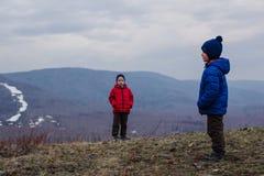 As crianças da idade pré-escolar nos revestimentos e nos chapéus estão no dia frio nevoento da montanha fotografia de stock