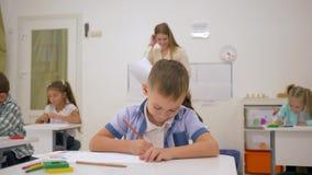 As crianças de escola primária tiram no papel com lápis coloridos em uma mesa com o professor novo na sala de aula clara filme
