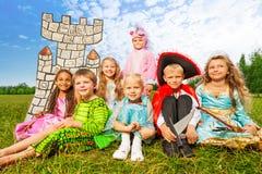 As crianças de sorriso em trajes do festival sentam-se perto Imagens de Stock Royalty Free
