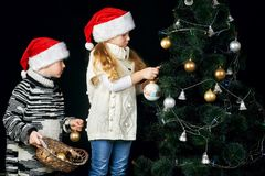 As crianças decoram a árvore de Natal na sala imagens de stock