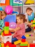 As crianças do grupo junto estão jogando com blocos no jardim de infância Fotografia de Stock