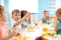 As crianças do jardim de infância têm um almoço As crianças têm um divertimento ao redor com alimento fotografia de stock