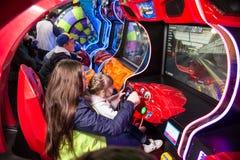 As crianças e os adultos jogam nos slots machines, atrações no shopping As famílias com crianças têm a arcada do divertimento e d fotos de stock