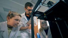 As crianças e um professor olham uma impressora 3D em um laboratório da escola 4K vídeos de arquivo