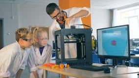 As crianças e um professor trabalham com uma impressora 3D em um laboratório, fim acima filme