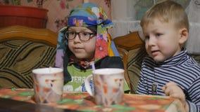 As crianças em casa que bebem o leite e olham o caderno filme