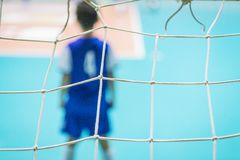 As crianças em equipes azuis treinam e jogam o futebol no salão fotos de stock