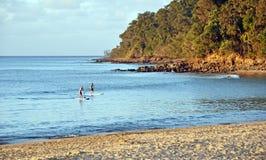 As crianças em placas de pá em Noosa dirigem a praia no por do sol, Queens imagem de stock royalty free