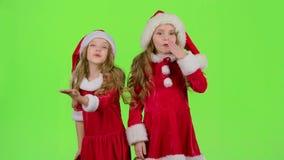 As crianças em tampões vermelhos do Natal enviam beijos do ar Tela verde vídeos de arquivo