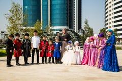 As crianças em trajes nacionais na flor estacionam na capital de Chechnya Imagens de Stock