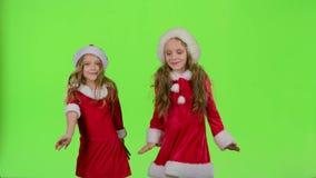As crianças em trajes vermelhos do ano novo estão dançando Tela verde video estoque
