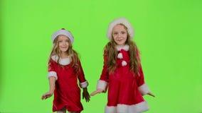 As crianças em trajes vermelhos do ano novo estão dançando Tela verde Movimento lento vídeos de arquivo