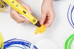 As crianças entregam guardar a pena amarela da impressão 3D com filamentos e fazem o artigo novo Fotografia de Stock Royalty Free