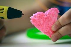 As crianças entregam guardar a pena amarela da impressão 3D com filamentos e fazem o coração no fundo branco Vista superior Copie Imagem de Stock