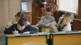 As crianças escrevem o assento em uma mesa vídeos de arquivo
