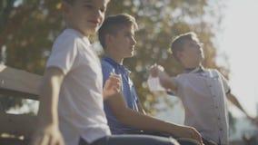 As crianças estão lançando os planos de papel que sentam-se em um banco fora Movimento lento filme