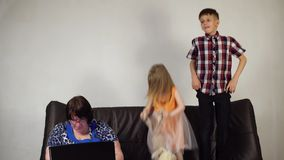 As crianças estão saltando no sofá, uma avó frustrante estão usando um portátil filme