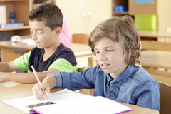 As crianças estão sentando-se na sala de aula Imagens de Stock