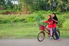 As crianças fêmeas de um malay novo montam uma bicicleta em sua cidade natal Cara do sorriso deles Veja um fundo da vila rural ma Imagens de Stock Royalty Free