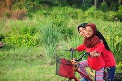 As crianças fêmeas de um malay novo montam uma bicicleta em sua cidade natal Cara do sorriso deles Veja um fundo da vila rural ma Foto de Stock