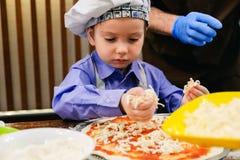 As crianças fazem a pizza Classe mestra para crianças em cozinhar a pizza italiana imagem de stock royalty free