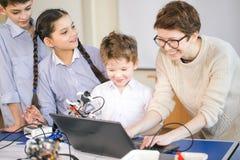 As crianças felizes aprendem a programação usando portáteis em classes do extracurricular fotografia de stock royalty free