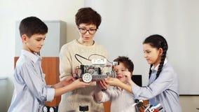 As crianças felizes aprendem a programação usando portáteis em classes do extracurricular