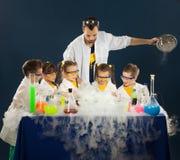 As crianças felizes com o cientista que faz a ciência experimentam no laboratório imagens de stock