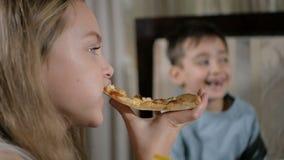 As crianças felizes comem a pizza no restaurante