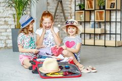 As crianças felizes embalam coisas em uma mala de viagem em uma viagem Conceito t Fotos de Stock