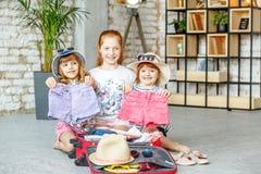 As crianças felizes embalam a roupa em uma mala de viagem em uma viagem Conceito Imagem de Stock