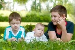 As crianças felizes encontram-se na grama verde no parque foto de stock