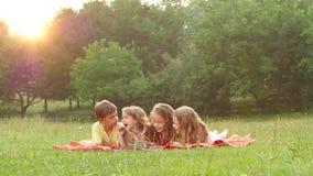 As crianças felizes folheiam através de um livro no jardim no gramado um o dia de verão Movimento lento filme