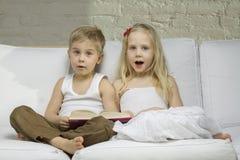 As crianças felizes leram um livro Fotos de Stock Royalty Free