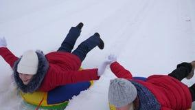 As crianças felizes montam a neve na estrada nevado e no riso com prazer Meninas que sledding no inverno e no sorriso cheerful video estoque