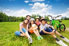 As crianças felizes nos capacetes sentam-se na grama e no sorriso Imagens de Stock