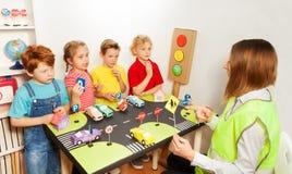 As crianças felizes que ensinam o tráfego assinam dentro o jardim de infância Fotografia de Stock