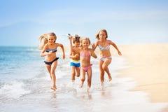As crianças felizes que jogam com brinquedo aplanam pelo mar imagens de stock