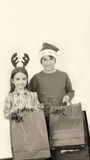 As crianças felizes que vestem o Natal vestem guardar os presentes, isolados no wh Fotografia de Stock
