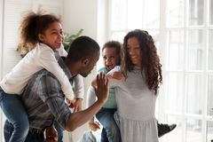 As crianças felizes rebocam os pais que jogam junto em casa fotografia de stock royalty free