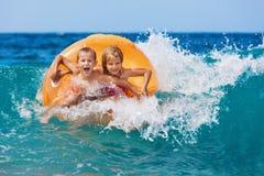 As crianças felizes têm o divertimento na ressaca do mar na praia imagem de stock