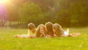 As crianças folheiam através de um livro no jardim no gramado um o dia de verão filme