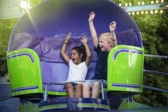As crianças gritando que apreciam um parque de diversões do verão do divertimento montam Fotografia de Stock